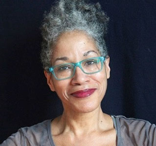 Headshot of Lifetime Arts Trainer, Asma Feyijinmi. She has light curly hair and dark eyes with glasses. She is smiling.