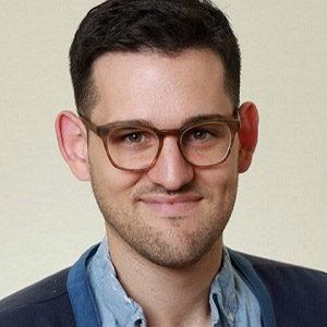 Headshot of teaching artist, Vinny Mraz. He has short dark brown hair and brown eyes with glasses. He is smiling.