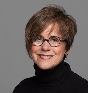 Headshot of Lifetime Arts Trainer, Lynda Monick-Isenberg. She has short brown hair, glasses, and is smiling.